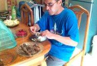 Di meja makan di dapur, saya  mencicipi ayam panggang buatan istri saya. Istri saya memotret sambil juga menggerogoti paha ayam kesukaannya