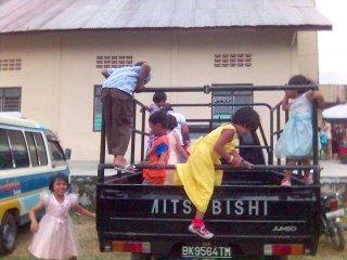 Anak-anak SM bermain di atas mobil di samping gereja. Bosan dengar khotbah ya?