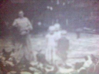 Ny Theis (Mrs Henriette) sedang memberi makan ternak mereka, disaksikan putra-putrinya. Sumber: Riwayat Hidup Pandita August Theis, 1987, Kolportase GKPS, A. Munthe