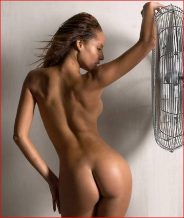 Naked brunette standing at fan