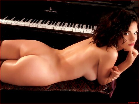 Naked woman laying on piano bench