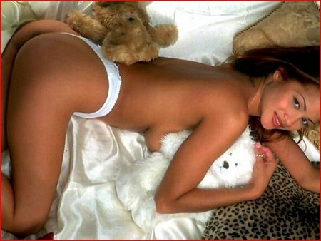 Sexy topless gal laying down with stuffed bears