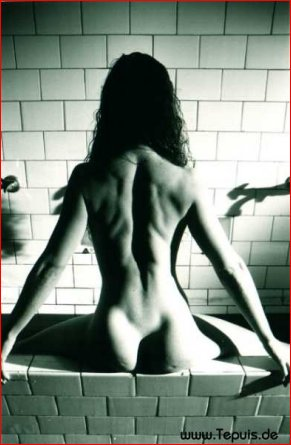 Nude babe showing ass sitting on brick wall