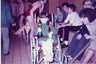 Me, aged 5, on a swimming pool side in my first, red, wheelchair, with my left leg in a full length cast, clutching a trophy