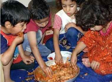 4 refugee children from Baghdad share a meal from a metal bowl at a refugee camp near Fallujah