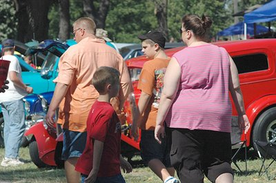 Image of overweight Americans at an outdoor car show