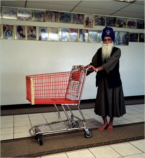 At the El Sobrante Gurdwara (a temple officially known as the Sikh Center of San Francisco Bay Area), a priest prepares to move groceries in the dining room. Behind him is a picture gallery of gurus.