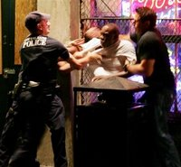 Police officers subdue a man on Conti Street near Bourbon Street in the French Quarter of New Orleans Saturday night, Oct. 8, 2005. Stolen from someone somewhere.