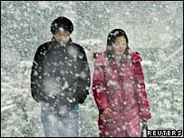 A Japanese couple walking in the snow.