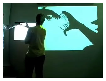 Image of two people creating shadow puppets, which are converted into monsters on a huge projected screen via a computer and camera.