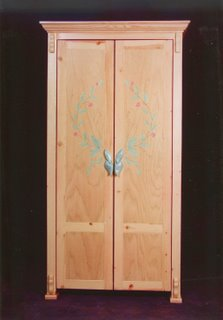 Pine cabinet with intarsia inlay and carved handles.