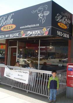 Tristan in front of Bella Pizza