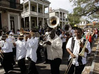 A band leads people down Esplanade Street during a second-line parade in New Orleans, Saturday.