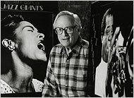 William P. Gottlieb in 1992, between two of his best-known photographs: portraits of Billie Holiday and Louis Armstrong.