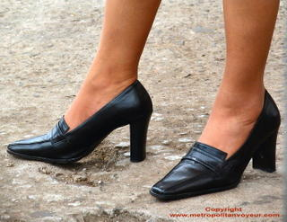 Black shiny new high heeled leather pumps with broad heel.