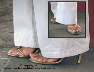 Glamour removing trousers from golden strap sandals