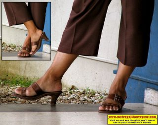 Brown eyelet equipped slip on sandals with brown trouser from a lady standing beside a payphone booth