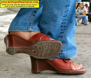 Red wedged heeled shoes with crossed legs and visible soles