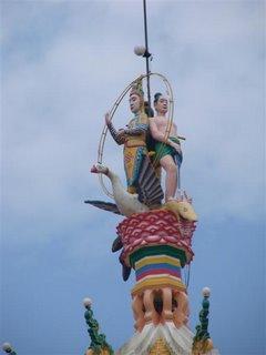 Parece piada. As estatuas de Buda e Jesus (de saia), lado a lado, em cima de uma ave Fenix e esmagando uma cobra com os pes