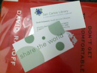 my business cards. the back says 'share the world', laying on top of David Rakoff's newest book