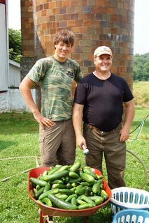 Jerry Dillon and Farmer posing behind a wheelbarrow of cucumbers.