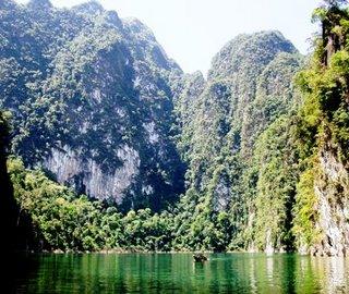 Rocks tower over a long tail boat, Khao Sok