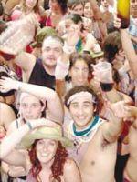 Un grupo de gente, empapado de vino y con las camisetas hechas trizas, saluda a la cámara