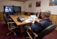 President George W. Bush is handed a map by Deputy Chief of Staff Joe Hagin, center, during a video teleconference with federal and state emergency management organizations on Hurricane Katrina from his Crawford, Texas ranch on Sunday August 28, 2005. White House photo by Paul Morse.