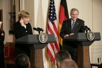Chancellor Angela Merkel of Germany, adjusts her earpiece as President George W. Bush begins his remarks during a joint press availability Friday, Jan. 13, 2006, in the East Room of the White House. White House photo by Eric Draper.