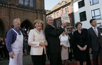 Standing with German Chancellor Angela Merkel, President George W. Bush holds up a ceremonial gift of a barrel of herring in Stralsund, Germany, Thursday, July 13, 2006. Mrs. Bush is pictured at the right. White House photo by Eric Draper.