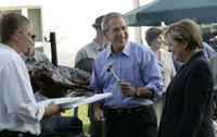 President George W. Bush enjoys a bit of barbeque Thursday, July 13, 2006, as he joins Chancellor Angela Merkel for a barbeque in Trinwillershagen. The President and Mrs. Laura Bush are scheduled to depart Germany Friday for St. Petersburg, Russia. White House photo by Eric Draper.