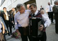 President George W. Bush puts his arm around an accordian player Thursday, July 13, 2006, after an evening barbeque in Trinwillershagen, Germany, hosted by Chancellor Angela Merkel. White House photo by Eric Draper.