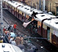People stand near the carriage of a train that was destroyed in a bomb explosion in Bombay, India, Tuesday, July 11, 2006. [© AP/WWP] from US State Department