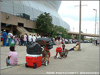 Residents are bringing their belongings and lining up to get into the Superdome which has been opened as a hurricane shelter in advance of hurricane Katrina. Most residents have evacuated the city and those left behind do not have transportation or have special needs. Marty Bahamonde/FEMA