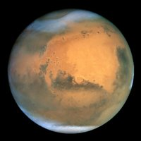 Frosty white water ice clouds and swirling orange dust storms above a vivid rusty landscape reveal Mars as a dynamic planet