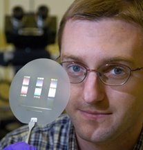Brian D. Iverson, a mechanical engineering doctoral student at Purdue, holds up a disk containing several 'micro-pump' cooling devices small enough to fit on a computer chip. The tiny pumps circulate coolant through channels etched into the chip. (Purdue News Service photo/David Umberger)