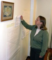 Robin M. examines handwritten responses to comments previously posted on her blog, printed out for the workshop.