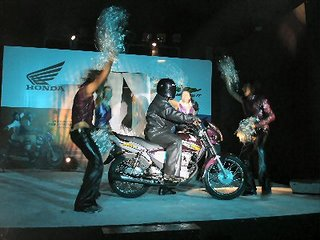 The girls hide behind the bike, much to the audiences display. Rider plays L-O-N-D-O-N statue