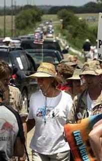 Cindy Sheehan, center, walks with supporter as dozens of cars drive on the road leading to President Bush's ranch near Crawford, Texas, Saturday. A grieving mother's anti-war protest entered its second week, gaining momentum and spurring counter rallies, as hundreds of people with conflicting opinions about the war in Iraq descended Saturday on a road leading to the Western White House.