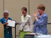 Photograph: Ann Sitkin receiving the Chapman Award from Janice Shull while outgoing TS Chair Cindy May looks on.