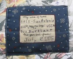 Photograph: Inscription by Sue Burkhart on one of the quilts.