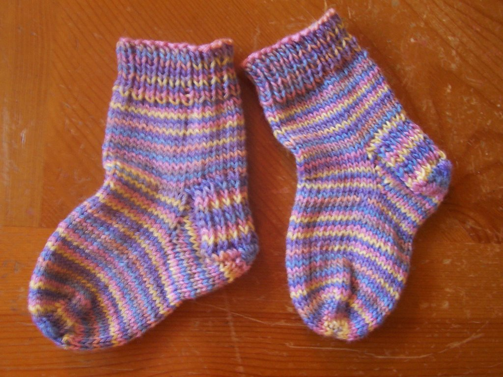 These nice fitting socks will stay on baby's feet even when happily kicking! Knit them with love in a wardrobe of colors. RED HEART® Soft Baby Steps™: 1 ball Elephant Susan Bates® Double-pointed needles: one set 5mm [US 8]; Yarn needle.