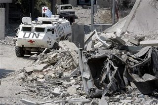 A U.N armoured car is parked near rubble after an Israeli air raid in Qana, 6 km (4 miles) from the port-city of Tyre (Soure), in south Lebanon, July 30, 2006. REUTERS/Zohra Bensemra