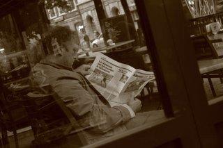 football, un homme lit les pages de sports dans un journal, place du marché à liège, belgique, photo dominique houcmant aka goldo graphisme