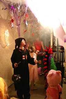 Jeff Ellico, dressed as Harry Potter, left, looks up as a mist is released into a doorway while trick-or-treating at Ann Williams, Rebecca Parks and Kristan Curry's elaborate Halloween-themed entranceway to their door Sunday night, Oct. 31, 2004, in Kingman, Ariz. Others trick-or-treating are Rachael Ellico, as Piglet, Annaka Lanegan, as a spikey monster, Alexia Lanegan, as a pink princess, and Aleah Lanegan, as Winnie the Pooh. (AP Photo/Kingman Daily Miner, J.C. Amberlyn)