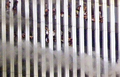 A close-up showing people looking out of the burning North tower of the World Trade Center. Shortly after the photo was taken this tower collapsed.
