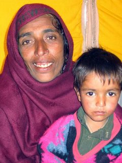 Gulzar, whose family died before her eyes, walked seven days to reach this tent village. Shown here with a surviving nephew.