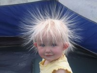 Kid with hair standing on ends caused by static electricity