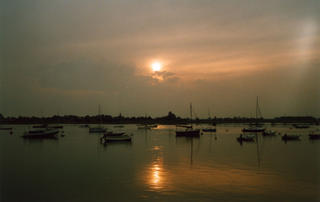 Sailing boats at anchor in the harbour at Bosham on a calm summer's evening.