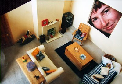 Modern dolls' house miniautre lounge, with a person looing through the window.